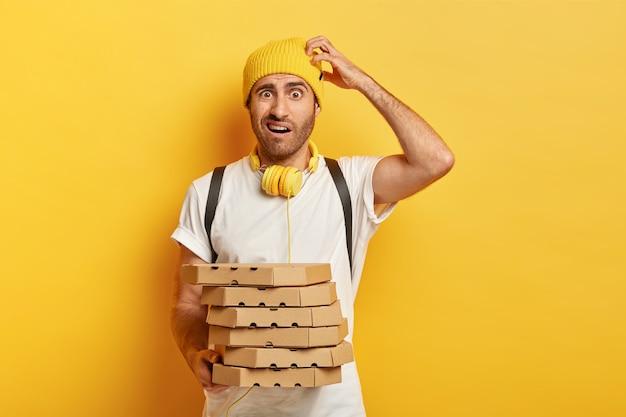 Фотография озадаченного сомнительного доставщика почесывает голову, держит коробки для пиццы на вынос, доставляет фаст-фуд покупателю, носит повседневную одежду, изолирована на желтой стене. концепция экспресс-доставки Бесплатные Фотографии