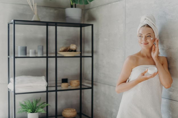 Фото расслабленной молодой женщины наносит крем для лица Premium Фотографии