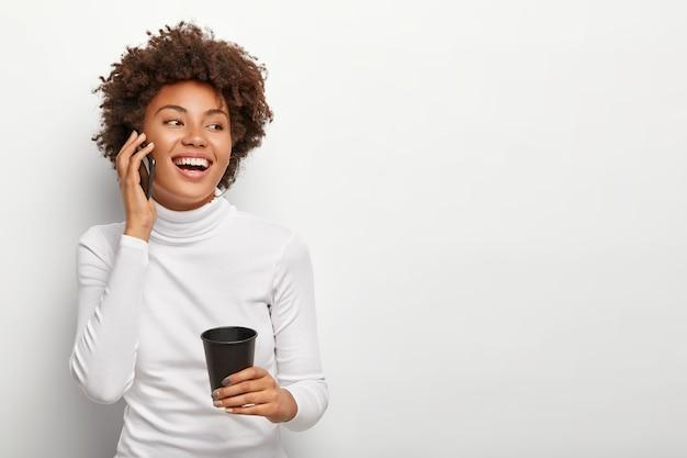 巻き毛のヘアカットで満足しているのんきな女性の写真、スマートフォンで話し、前向きに脇を向いて、テイクアウトのコーヒーを飲み、活発な会話中に気分が良い。人とライフスタイル 無料写真