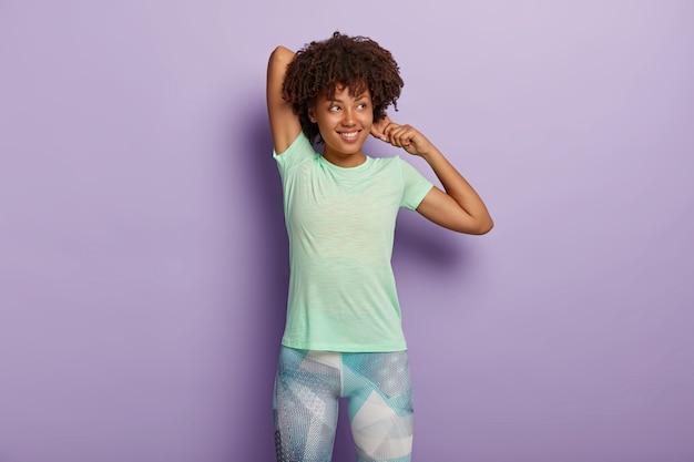 満足している暗い肌の女性の写真は、手を伸ばし、フィットネストレーニングの前にウォームアップし、スポーツウェアを着用し、柔軟性があり、脇に焦点を合わせ、紫色の壁に隔離されています。ワークアウトの概念 無料写真