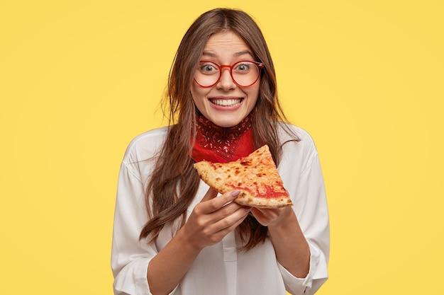 Фотография довольной женщины держит кусок пиццы, чувствует себя довольной, проводя свободное время с друзьями в пиццерии, выглядит довольной прямо в повседневной одежде, изолированной за желтой стеной. обед Бесплатные Фотографии