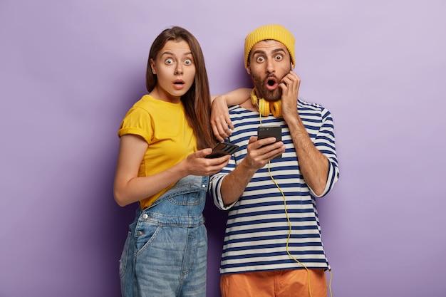 무서워하는 여자와 남자의 사진은 휴대 전화로 포즈를 취하고 놀라운 소식에 충격을 받고 예기치 않은 업데이트로 당황하고 무언가를 두려워합니다. 무료 사진