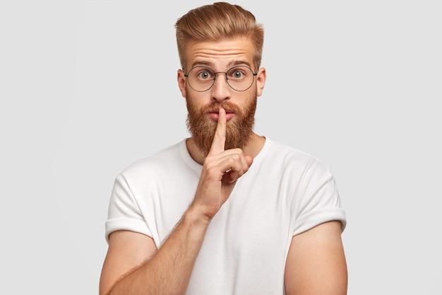 秘密の生姜のスタイリッシュな男性の男の写真は沈黙の兆候を示し、表情を驚かせ、秘密を明かすことを恐れ、カジュアルな服装で、白い壁に一人でポーズをとる。人と秘密の概念 無料写真