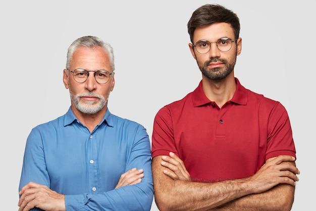 Фотография серьезных, уверенных в себе коллег-мужчин, скрестив руки, думает о новом проекте, принадлежит к разной возрастной группе, имеет общие интересы в сфере бизнеса, изолирована на белой стене Бесплатные Фотографии
