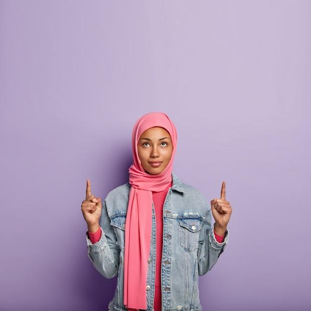 심각한 젊은 무슬림 여성의 사진은 앞쪽 손가락으로 위쪽을 가리키고, 분홍색 스카프를 착용하고, 분홍색과 데님 재킷을 입고 보라색 벽 위에 절연되어 있습니다. 사람, 광고 및 홍보. 무료 사진