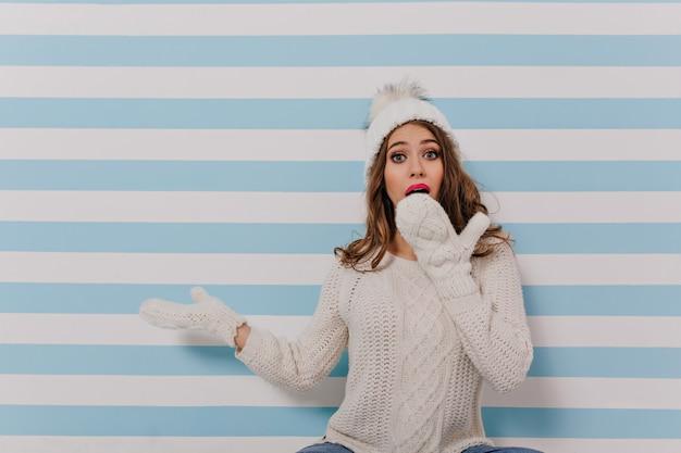 孤立した縞模様の壁に座っている女の子の写真。ニットのジャンパーを着た若い女性が手で驚いて口を閉じる 無料写真