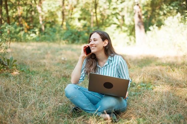 公園の芝生の上に座っている間電話で話している笑顔で魅力的な女性の写真。 Premium写真