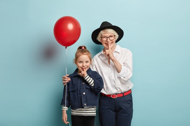 笑顔の小さなかわいい女の子と年配の女性の写真は、ハッシュサインを示し、秘密を伝え、嬉しい表情を持ち、興奮し、お祝いのイベントに来て、青い壁に隔離されています。黙って、静かにして 無料写真