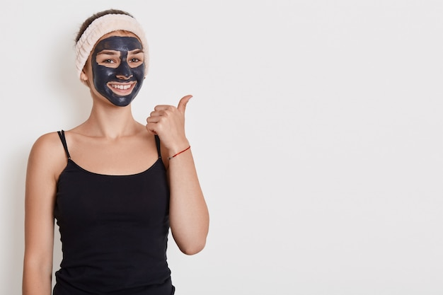 笑顔の女性の写真は、顔のマスクが付いた黒いtシャツとヘアバンドを身に着けている、自宅で美容手順、肯定的な表情、白い壁に分離された親指で脇にポイントがあります。 無料写真
