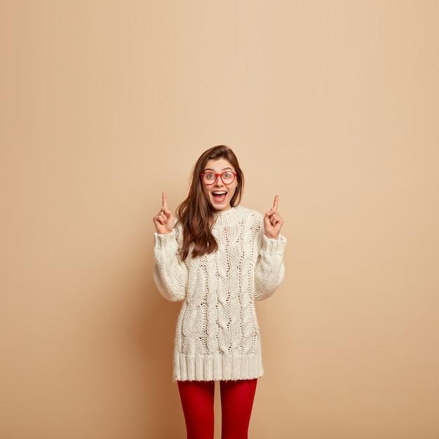 만족스러운 표정으로 웃는 여자의 사진, 행복하게 웃고, 위의 것을 보여주고, 위쪽을 가리키고, 광고 콘텐츠를위한 공간을 보여주고, 니트 흰색 스웨터를 입고, 투명 안경을 착용합니다. 무료 사진