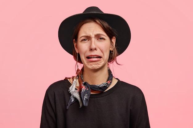 На фото грустная женщина плачет от горя, сжимает губы и недовольна, носит элегантную шляпу и свитер, позирует на фоне розовой стены. Бесплатные Фотографии