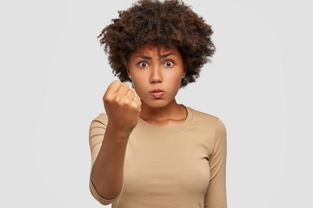 Фото строгой серьезной молодой женщины доминирует, показывает кулак в камеру, угрожает или предупреждает о чем-то, злится Бесплатные Фотографии
