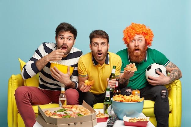 愚かな親友の写真は、テレビの画面を見つめ、ビールを飲み、おいしいピザを食べ、サッカーの試合の予想外の結果にショックを受け、快適な黄色いソファに座って、試合に負け、青で隔離 無料写真