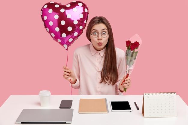 驚いた美しい若い女性の写真は唇を丸く保ち、風船とバラを運び、眼鏡を通して見つめます 無料写真