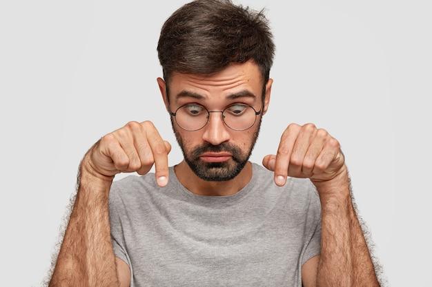 Фотография удивленного мужчины европеоидной расы с заторможенными глазами, щетиной, указывает вниз, потрясенно смотрит, небрежно одетый, изолированный на белой стене люди, удивление и недоверие. Бесплатные Фотографии