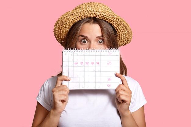 Фотография удивленной темноволосой женщины прячется за календарем менструального цикла, носит повседневную белую футболку и соломенную шляпу, в шоке от даты овуляции, изолирован на розовом, контролирует менструацию Premium Фотографии