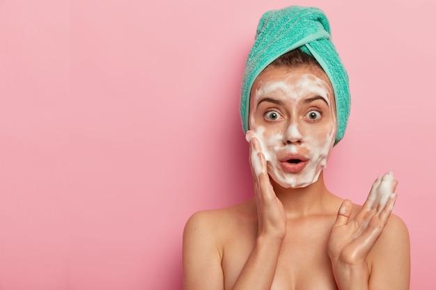 놀란 유럽 여성의 사진은 거품 젤로 얼굴을 씻고, 상쾌한 피부를 원하고, 토플리스를 서고, 젖은 머리카락에 수건을 감싸고, 분홍색 배경에 포즈를 취하고, 여유 공간을 제쳐두고 무료 사진