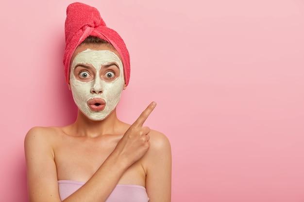 놀란 말을 못하는 여자의 사진은 얼굴 마스크를 쓰고 집에서 미용 절차를 가지고 있으며 충격적인 표정을 짓고 검지 손가락으로 옆으로 가리키며 젖은 머리카락에 수건을 감았습니다. 무료 사진