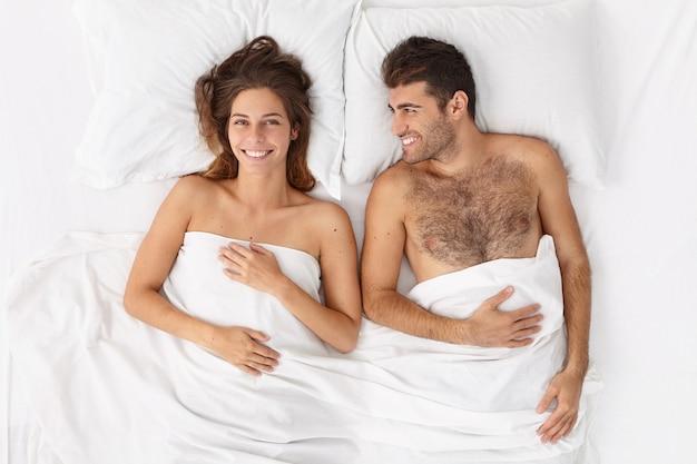 달콤한 부부의 사진은 흰 담요 아래 침대에 누워, 행복하게 미소 짓고, 함께 게으른 하루를 즐기고, 휴식을 취하고, 건강한 수면 후 깨어 있습니다. 신혼 부부는 결혼식 밤이 있습니다. 위에서 평면도 무료 사진