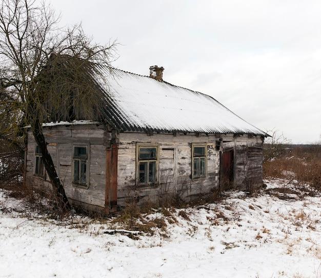 폭설 후 눈으로 덮여 오래된 붕괴 한 집의 사진 프리미엄 사진