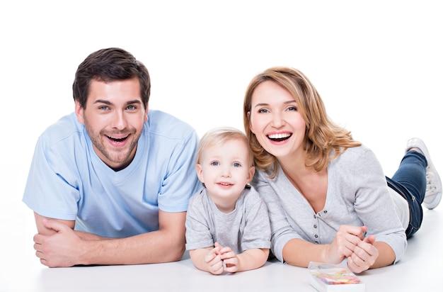 작은 아이가 바닥에 누워 웃는 젊은 부모의 사진-절연 무료 사진