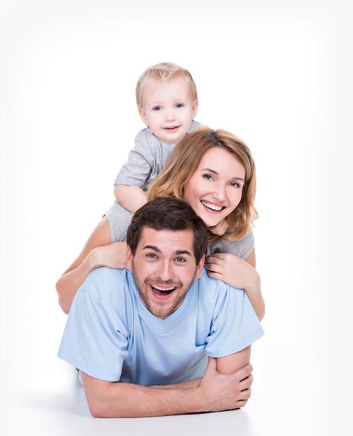 Фотография улыбающихся молодых родителей с маленьким ребенком, лежащим на полу - изолированные Бесплатные Фотографии
