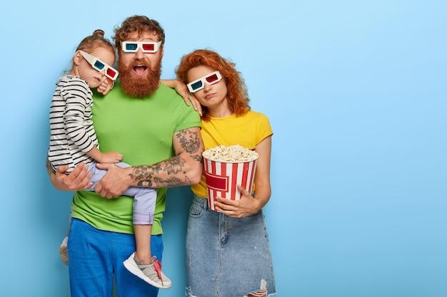 Фотография уставшей дочери и мамы наклоняется к мужу, который смотрит с впечатленным счастливым выражением лица, проводит свободное время в кино, часами смотрит фильм, носит трехмерные очки, ест попкорн в ведре Бесплатные Фотографии