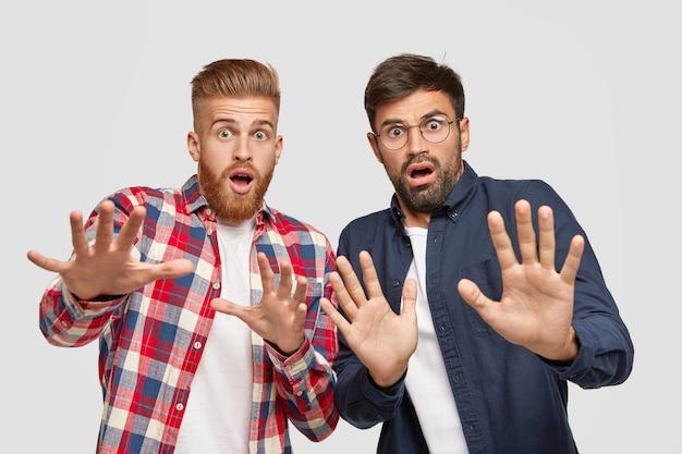 На фото двое мужчин испуганные лица, испуганные жесты ладонями, пытающиеся защититься от чего-то плохого Бесплатные Фотографии