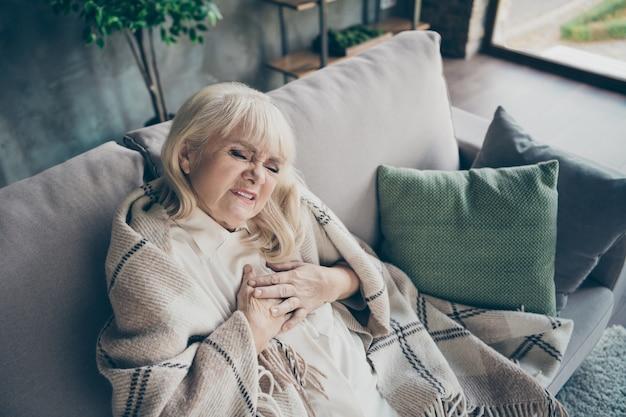 Фотография седой пожилой бабушки в отчаянии, держащей грудную зону, сердечные трудности, боязнь сердечного приступа, сидя на диване, накрытом пледом, в гостиной, в помещении Premium Фотографии