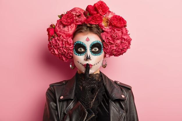 伝統的な化粧と髪に花をつけた女性の写真は、静けさのジェスチャーをし、人差し指を塗られた唇の上に保ち、ひどい死のパーティーの準備をし、黒い服を着て、ピンクで隔離されます 無料写真