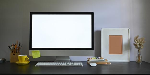 작업 공간 빈 화면 컴퓨터 모니터의 사진 책상에 퍼 팅과 액자, 연필 홀더, 책의 스택, 무선 마우스, 키보드, 커피 컵과 꽃병에 야생 잔디로 둘러싸인. 프리미엄 사진