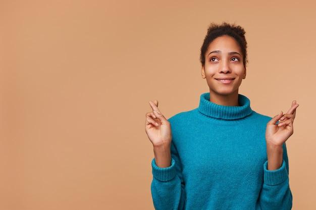 Фотография молодой афро-американской женщины в синем свитере с вьющимися темными волосами. глядя вверх, скрестив пальцы и загадывая желание. изолированные на фоне biege с copyspace. Бесплатные Фотографии