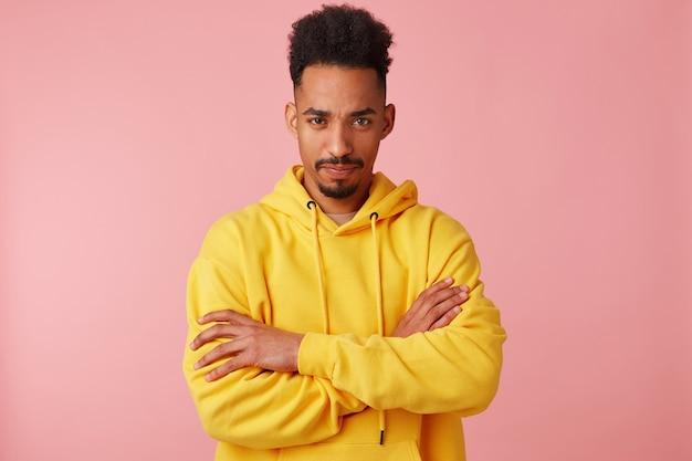 黄色いパーカーを着た、気分を害した、腕を組んで立っている若い不機嫌なアフリカ系アメリカ人の男の写真。 無料写真