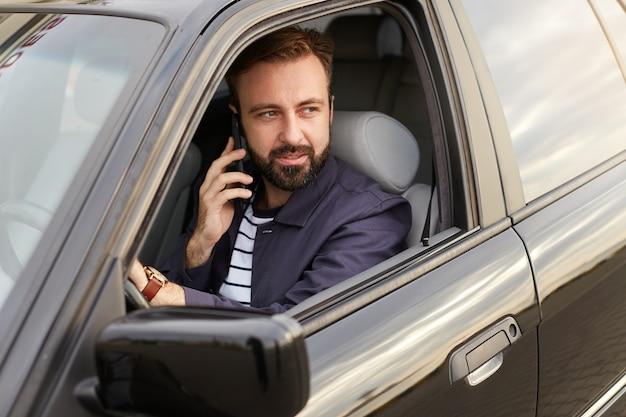 青いジャケットとストライプのtシャツを着た若いハンサムな成功したひげを生やした男の写真は、車のホイールの後ろに座って、携帯電話で友人に電話し、目をそらします。 無料写真