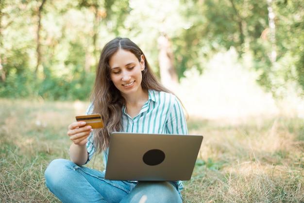 カードとラップトップでオンラインwebバンキングを作る若い幸せな女の写真。 Premium写真
