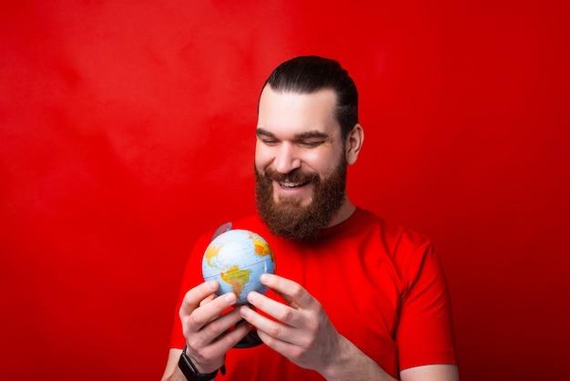 글로브, 세계 평화의 날을 들고 수염을 가진 젊은 남자의 사진 프리미엄 사진
