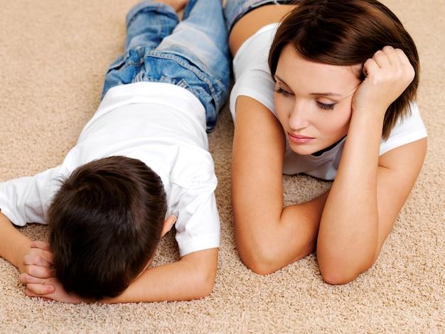 床に横たわっている若い母親とその不従順な有罪の泣いている息子の写真 無料写真