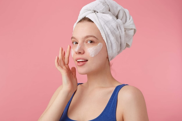 샤워 후 그녀의 머리에 수건으로 자연의 아름다움을 가진 젊은 좋은 기쁜 아가씨의 사진은 서서 얼굴 크림을 바르고 멀리 보입니다. 무료 사진