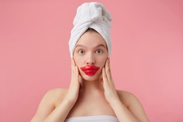 彼女の頭にタオルをつけてシャワーを浴びた後の若い驚いた女性の写真は、目を大きく開いて、唇にパッチを当て、ニュースを聞き、手のひらで頬に触れ、立っています。 無料写真