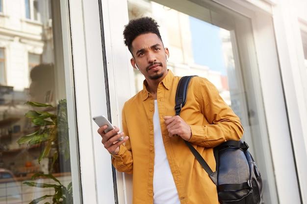 Фотография молодого мыслящего афроамериканца в желтой рубашке, идущего по улице, держащего телефон, слушающего новый подкаст, выглядит сомнительным. Бесплатные Фотографии