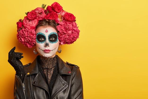 若い女性の写真は、頭蓋骨に似せて顔を美しく描いており、黒い革のジャケットと手袋を着用し、赤い芳香の花で作られた花輪を着用しています 無料写真