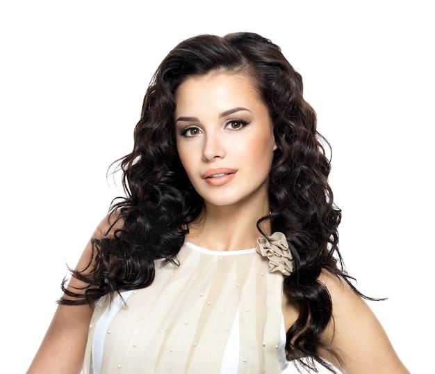 아름다움 긴 곱슬 머리를 가진 젊은 여자의 사진. 스튜디오에서 포즈를 취하는 패션 모델. 무료 사진