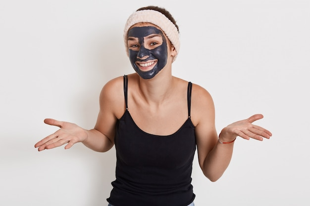 手のひらを脇に広げて魅力的な笑顔を持つ若い女性の写真は、無力なジェスチャーを示し、しわを減らすための栄養マスクを着用し、白い壁にポーズをとります。 無料写真