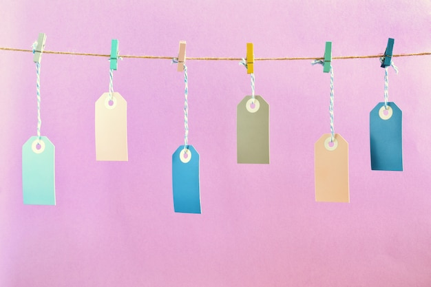 A photo on a pale lilac background. on the rope, with crumpled colored clothespins Premium Photo