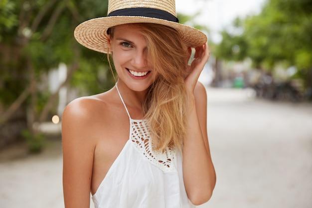 La foto dell'adorabile modella femminile indossa un abito bianco e un cappello di paglia estivo, cammina all'aperto, gode di un clima caldo e splendente, ha la pelle abbronzata, denti perfetti Foto Gratuite