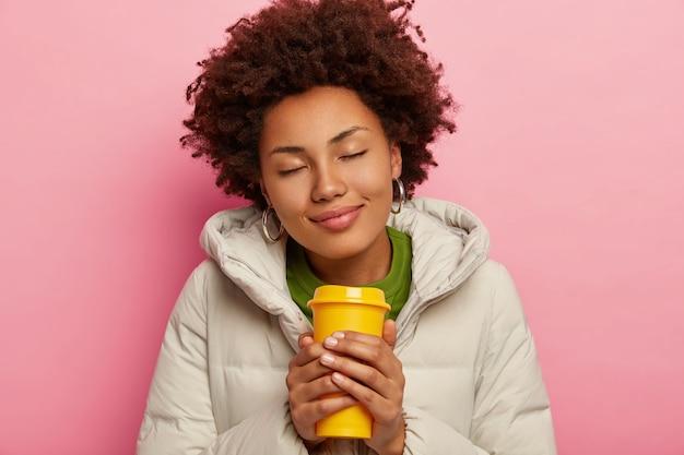 Foto di felice bella donna riccia indossa un cappotto caldo con cappuccio, beve caffè caldo, chiude gli occhi, isolato su sfondo rosa. Foto Gratuite