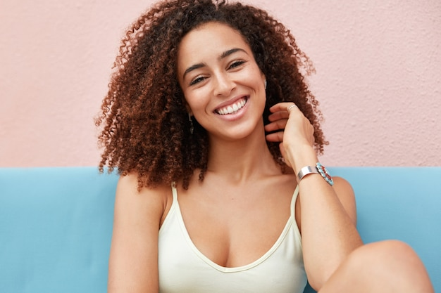 Photo of positive smiling woman with broad charming smile dressed casually and recreats at home, feels relaxed and comfortable Free Photo