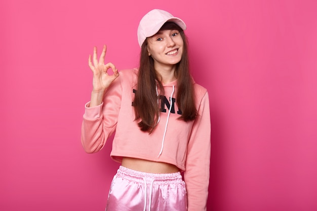 Photo of pretty attractive lady wearing rosy sport pullover, sweatpants, cap, shows okay sign Free Photo