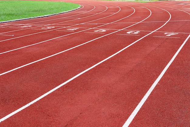 Photo of red running track for competition or exercise, as background. sports concept. Premium Photo