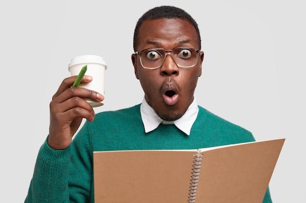 La foto di un ragazzo di colore emotivo e spaventato sembra stupore, porta caffè da asporto, scrive appunti su un taccuino, tiene la bocca tonda, vestito con disinvoltura Foto Gratuite